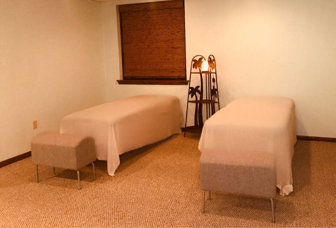 Two massage tables in the center of a room.